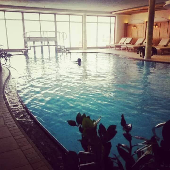 La grande piscina dell'Hotel Alpen Testin con area relax
