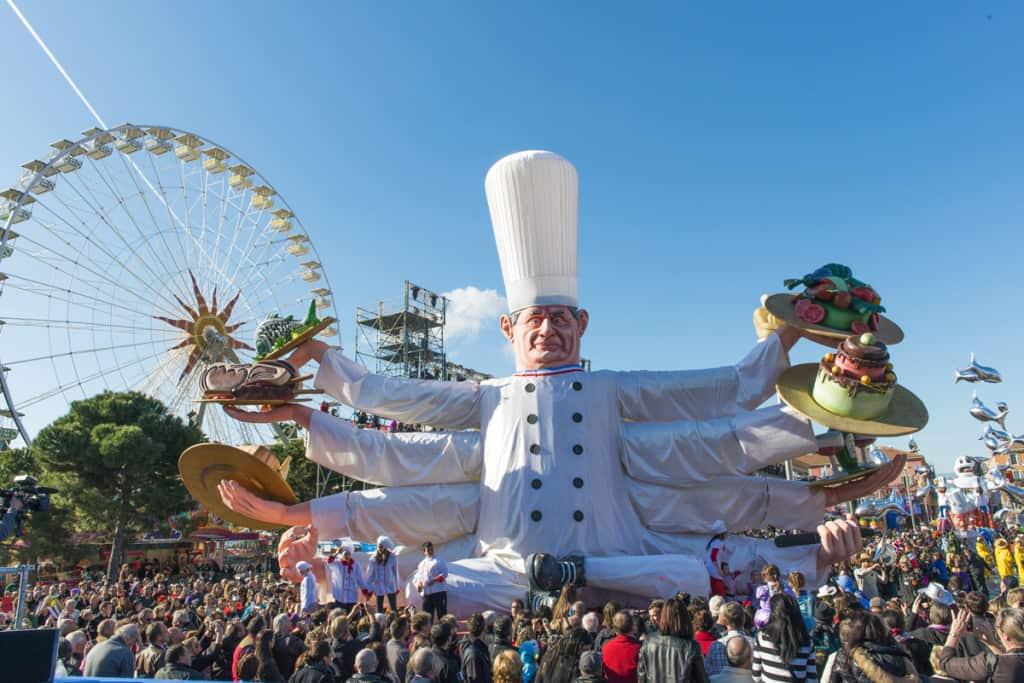 Uno dei bellissimi carri del Carnevale di Nizza, con un grande cuoco e sullo sfondo la ruota panoramica